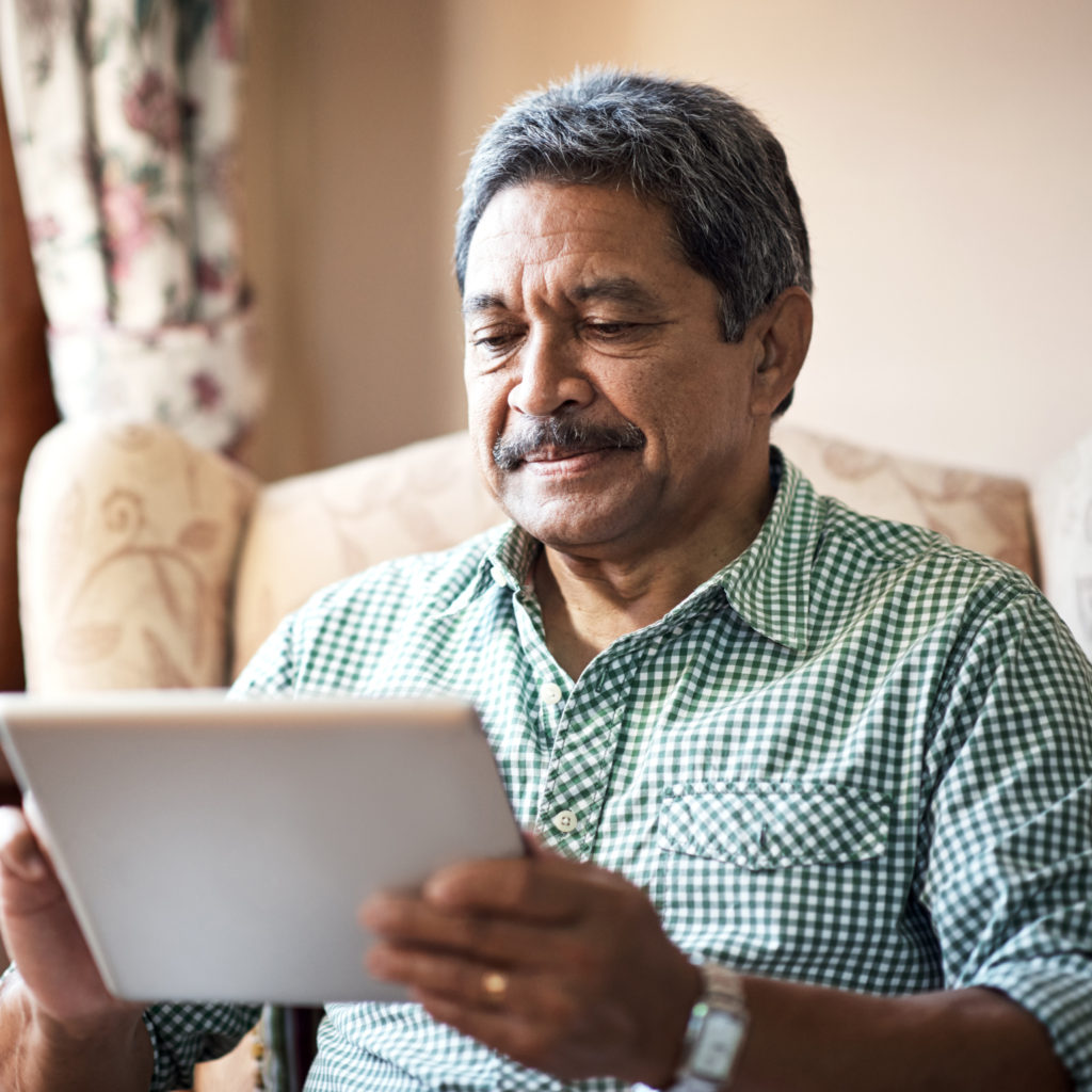 Senior man using his digital tablet while relaxing at home